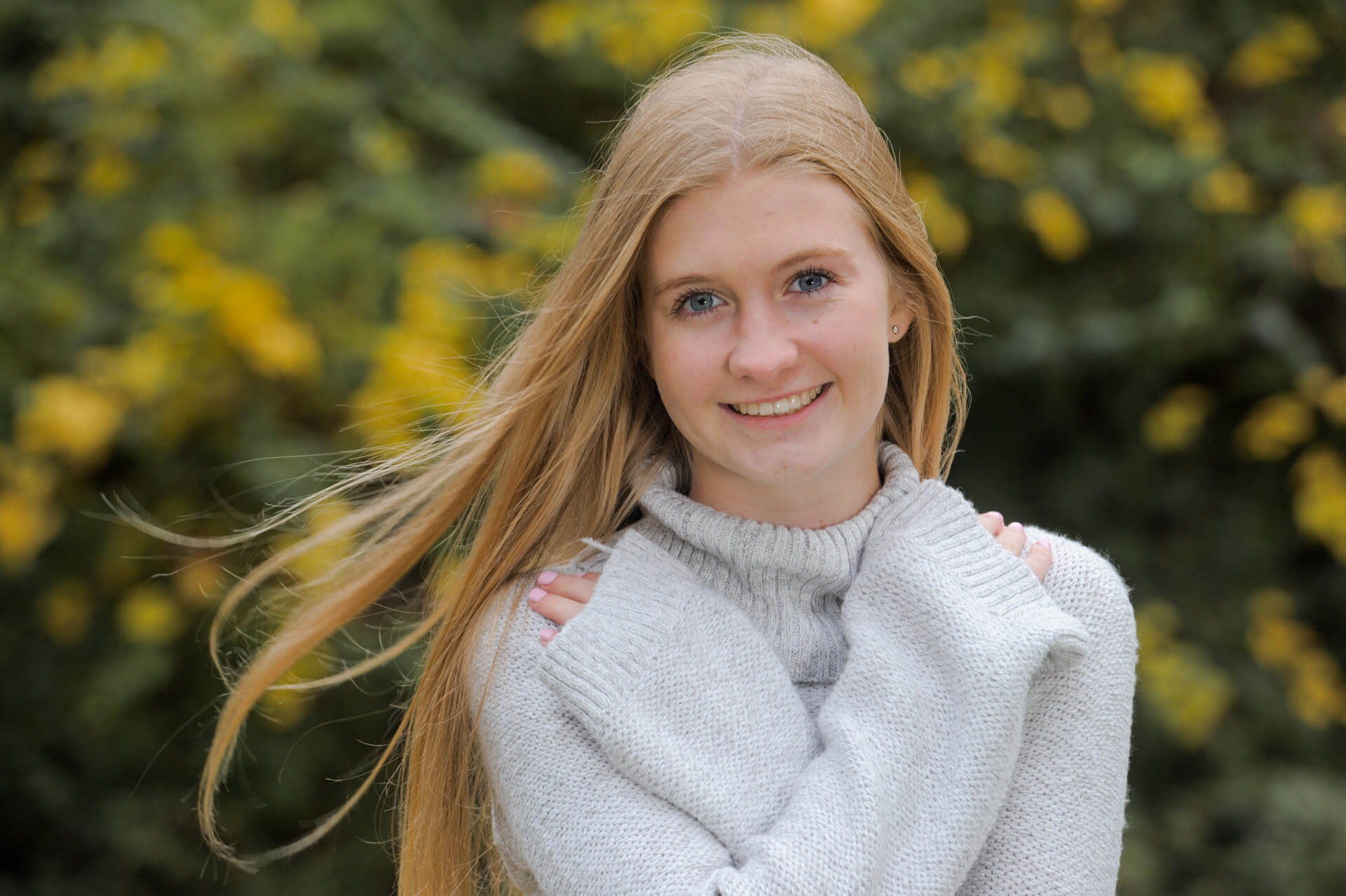 Troy High senior poses in in the fall near Rochester, Michigan for her fun, relaxed and affordable senior photos.