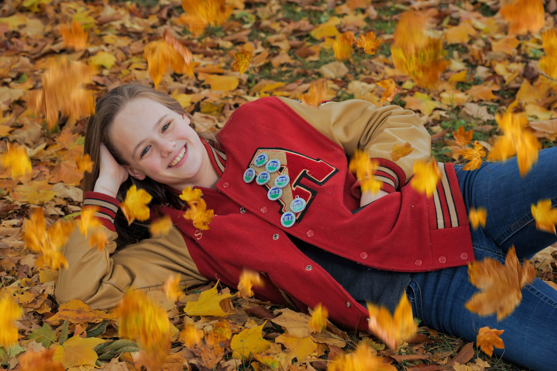A Troy Athens senior laying in the leaves at a park near Rochester Michigan for her senior photos.