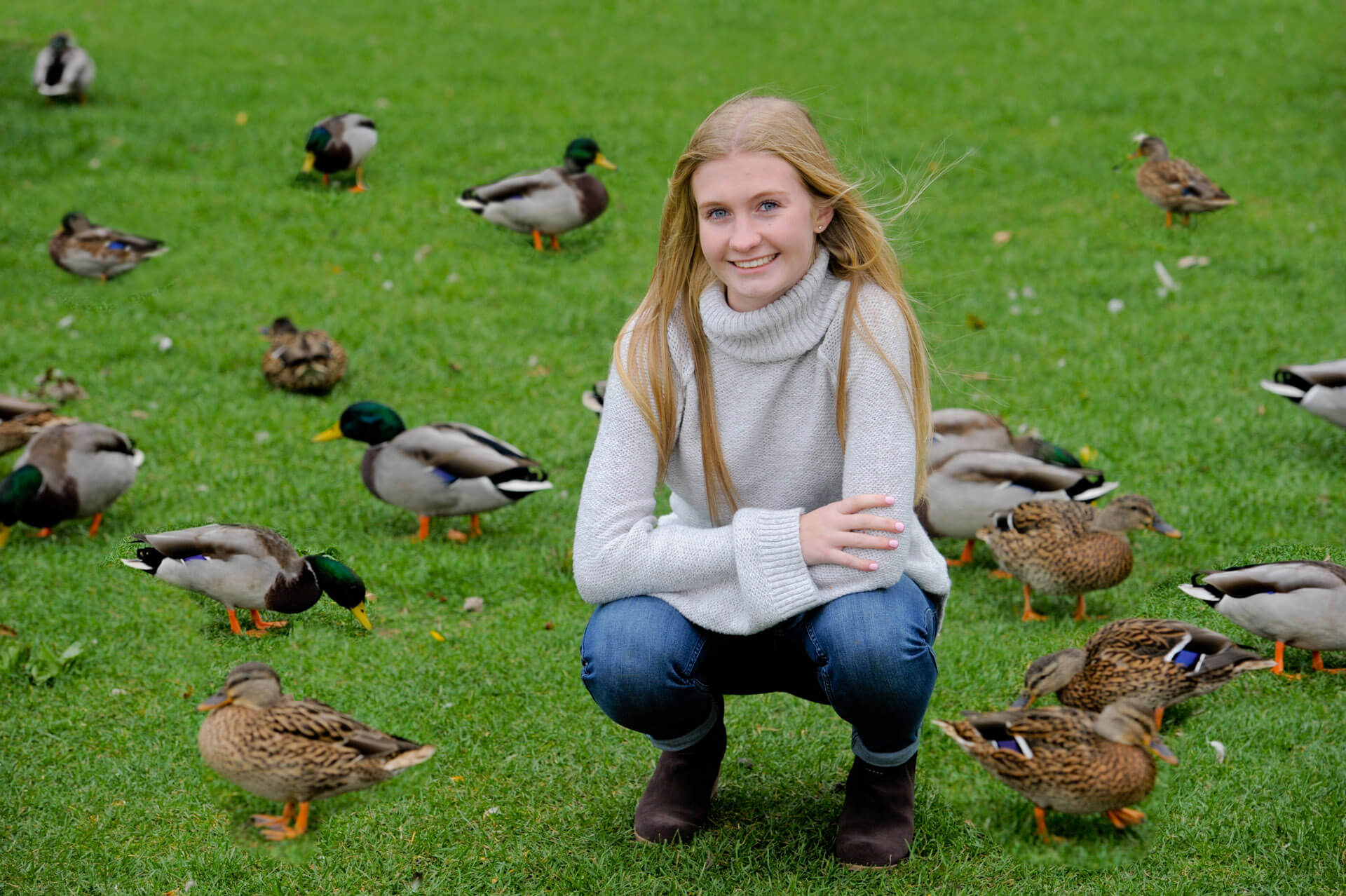 Troy High senior plays with ducks at the end of her affordable senior photography session near Rochester, Michigan.