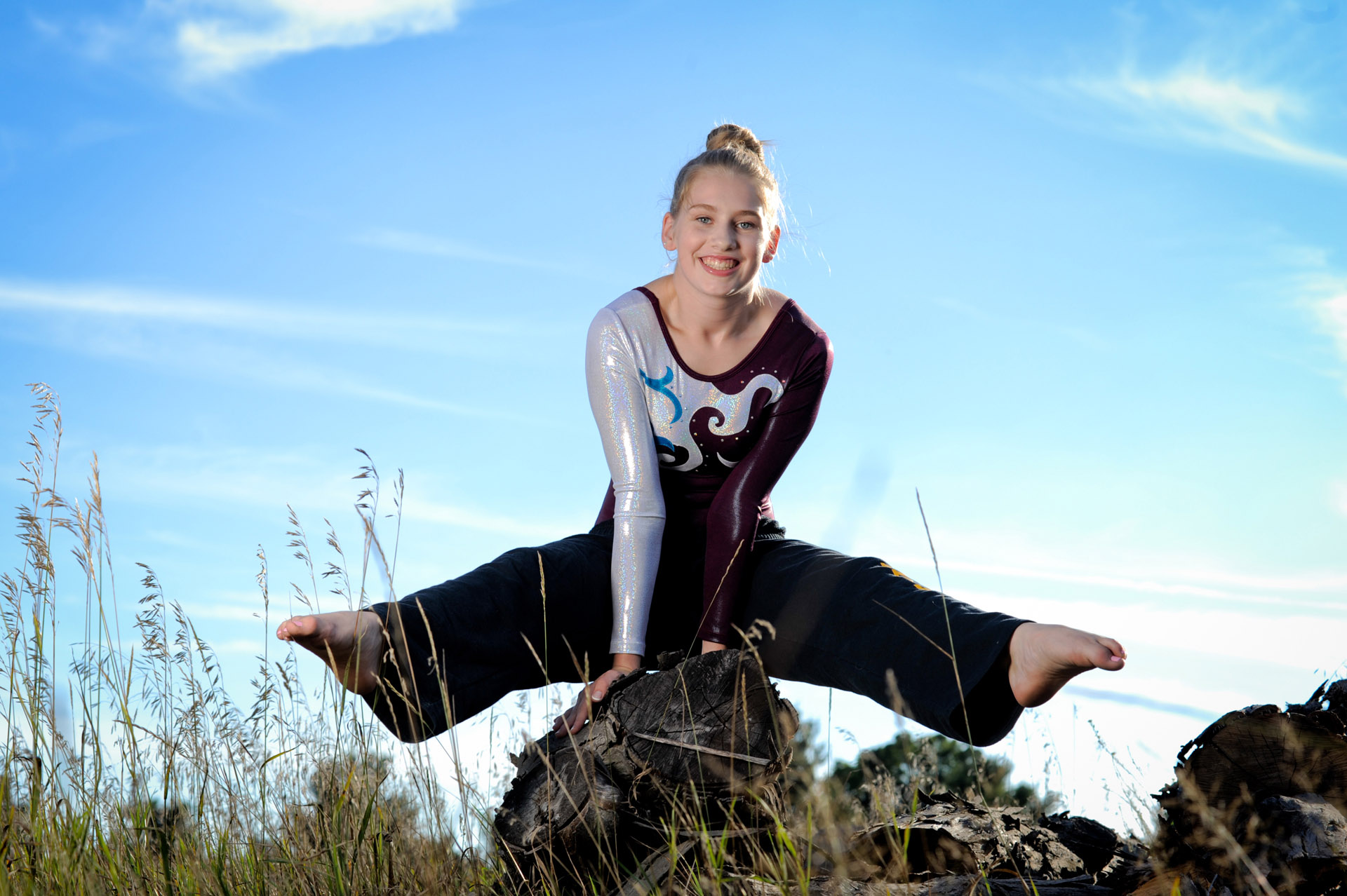 Troy, Michigan senior pictures photo taken of the high school gymnast senior using a log pile as gymnastic's equipment for her senior pictures in Troy, Michigan.