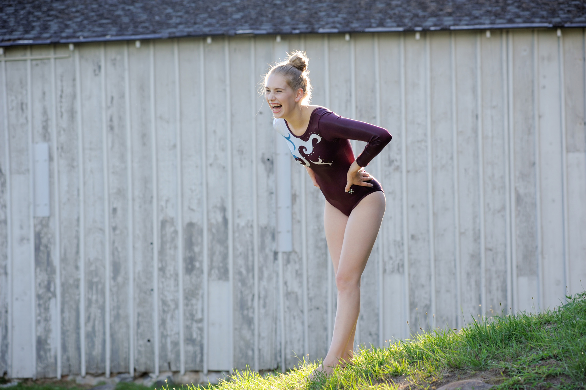 Troy , Michigan senior pictures photo of a high school gymnast senior laughs at the strangeness of going gymnastics on location for her senior pictures in Troy, Michigan.