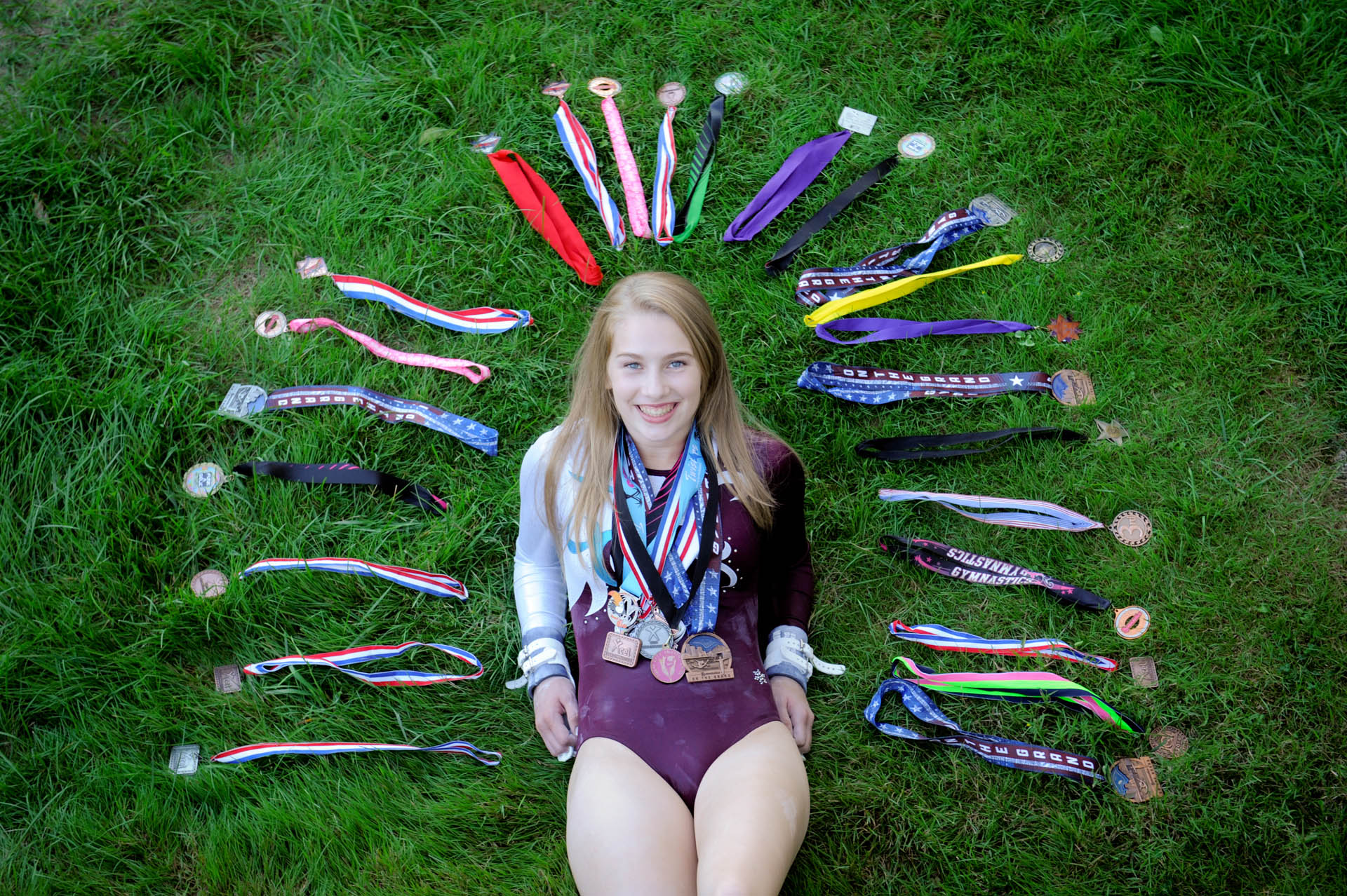 Troy , Michigan senior photographer shows a high school gymnast senior poses with many of her many ribbons for her senior pictures in Troy, Michigan.