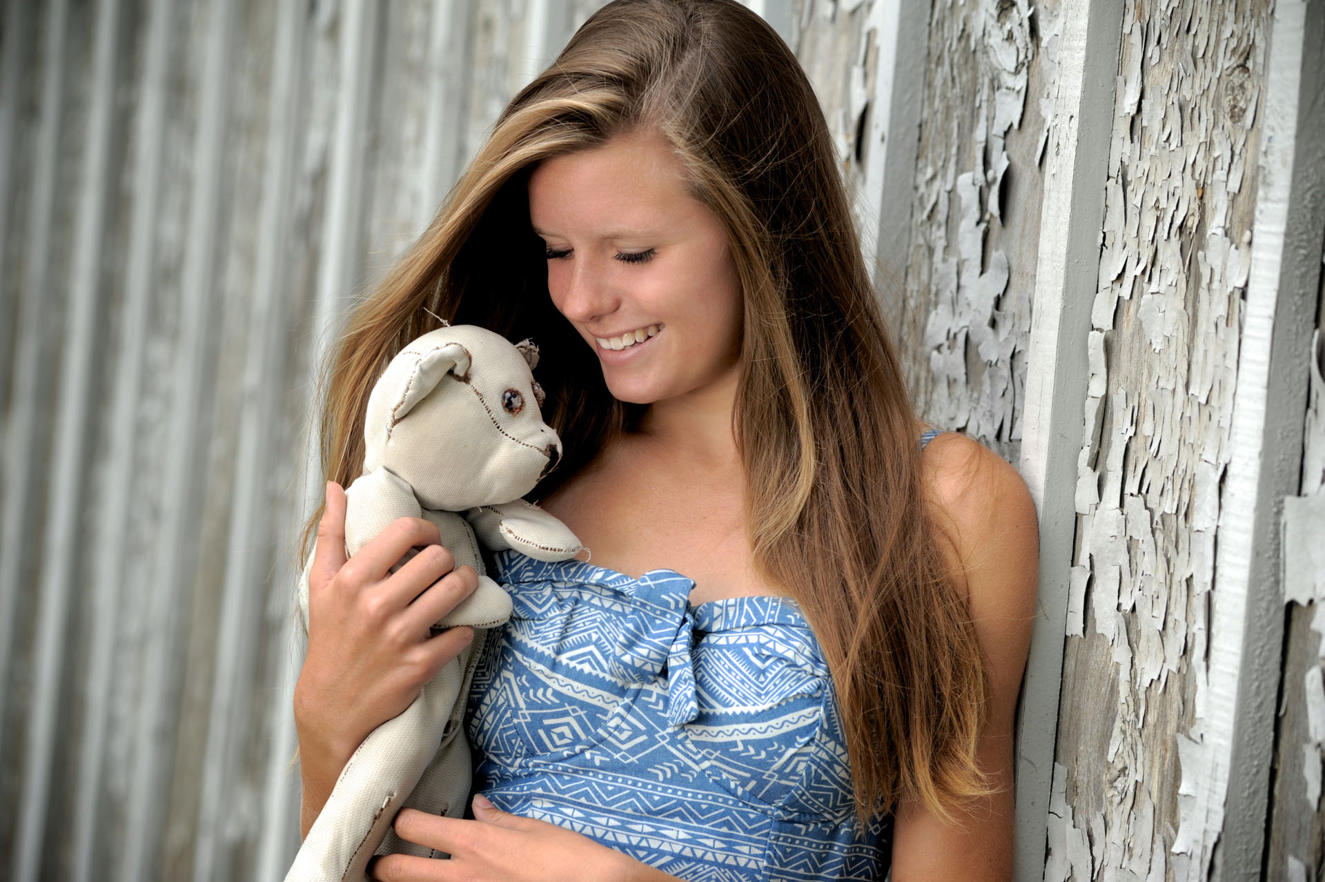 Troy , Michigan senior photographer's photo taken as the high school senior plays with her old stuffed animal for her their senior pictures in Troy, Michigan.