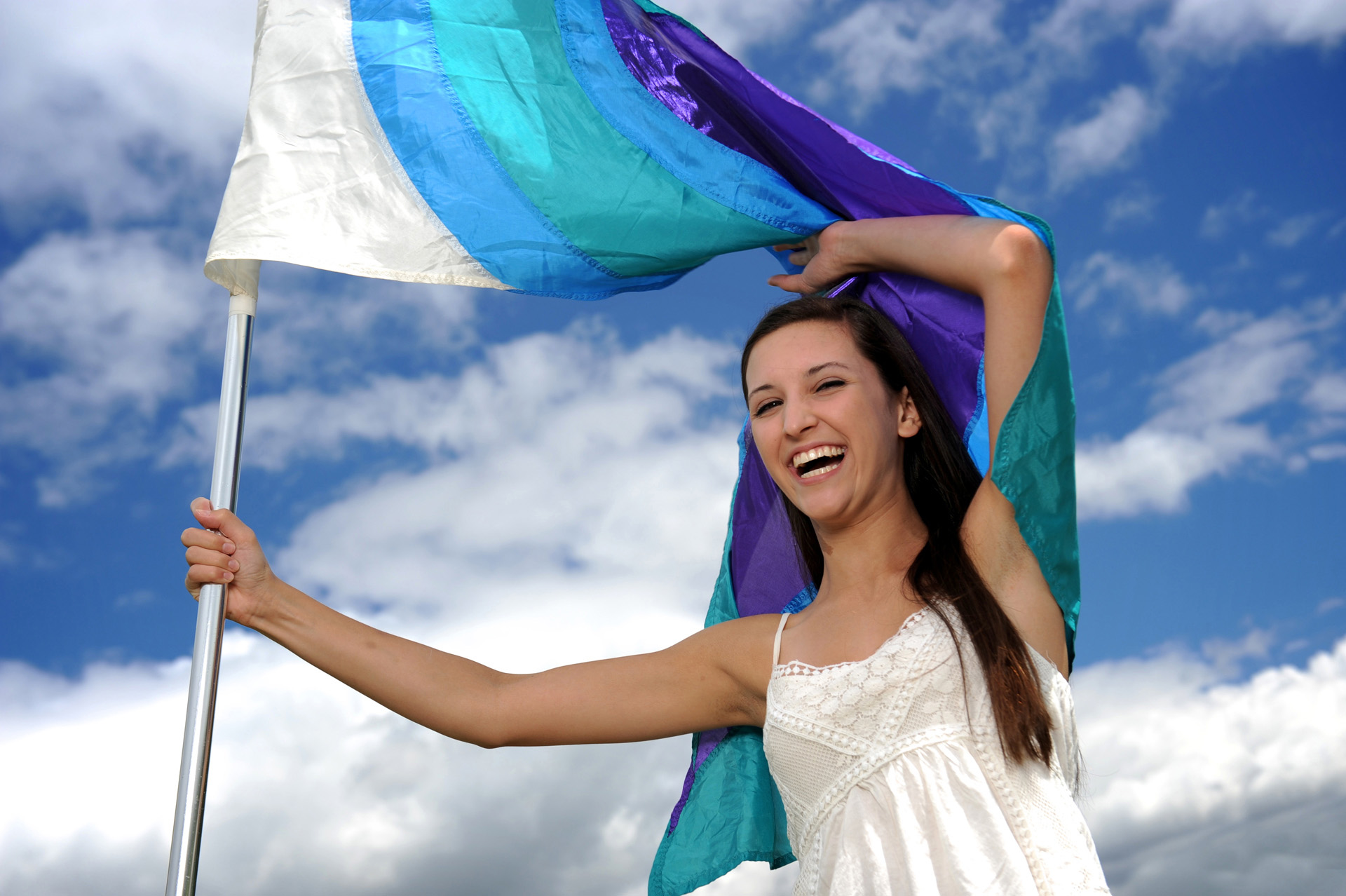 Troy , Michigan senior photographer shows a high school senior showing off her color guard flags during her Troy Senior Photo shoot.